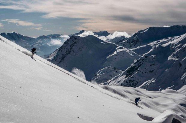 Eine Person fährt mit Ski den verschneiten Hang nach unten