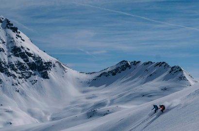 Eine Person fährt mit Skiern den Hang hinunter