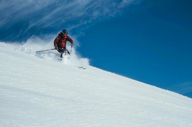 Ein Skifahrer fährt durch den Pulverschnee