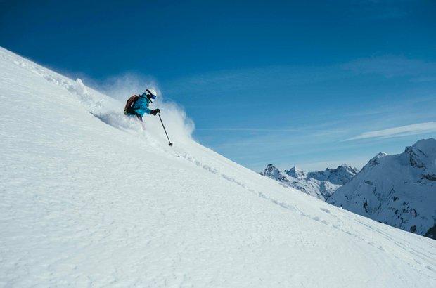 Ein Skifahrer macht einen Abfahrt im Tiefschnee